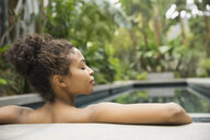 Woman resting at the edge of swimming pool - HEROF00063