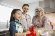 Three generation family baking together in kitchen - HEROF00459