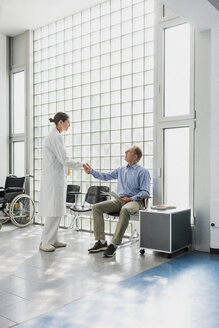 Doctor greeting, shaking hands with patient in clinic waiting room - FSIF03431