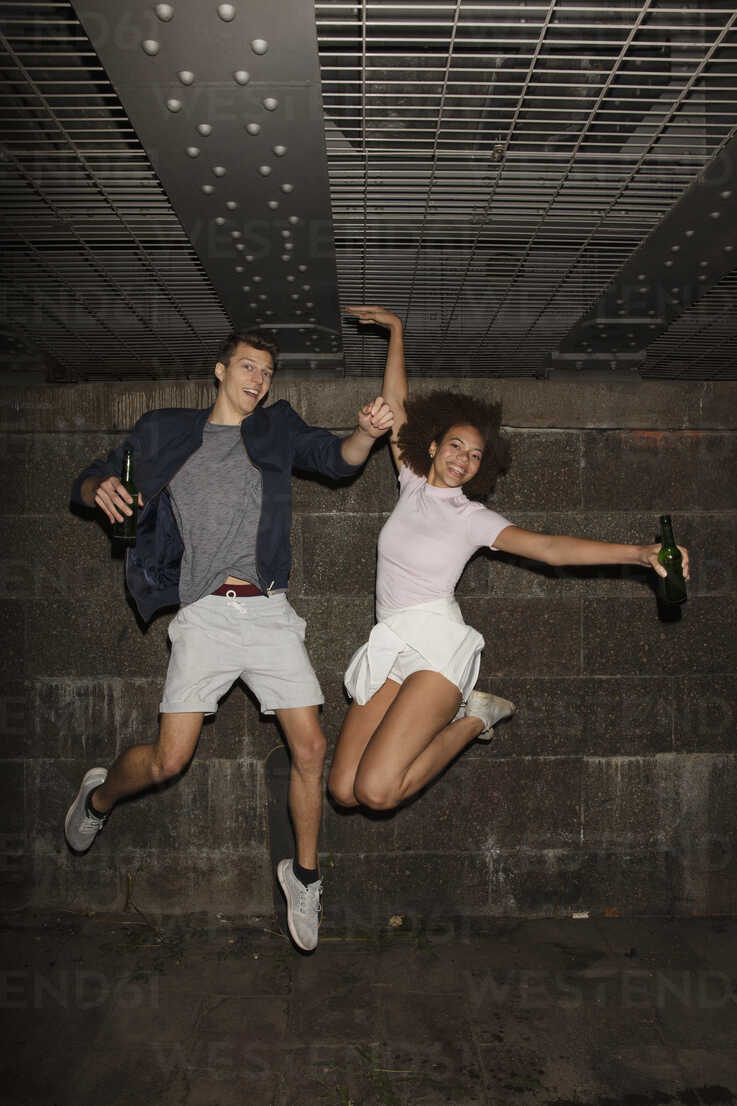 Portrait exuberant young couple drinking beer and jumping - FSIF03446 - Carl Smith/Westend61