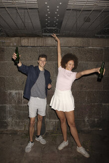 Portrait exuberant young couple drinking beer in basement - FSIF03461