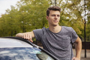 Portrait young man leaning on car, looking away - FSIF03464