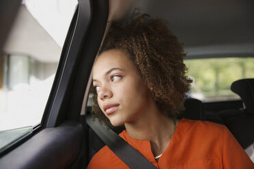 Thoughtful young woman riding in car, looking out window - FSIF03467