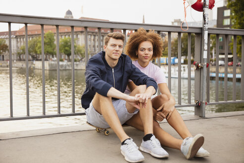 Portrait young couple sitting on skateboard on urban bridge - FSIF03476