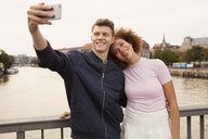 Affectionate young couple with smart phone taking selfie on urban bridge - FSIF03479