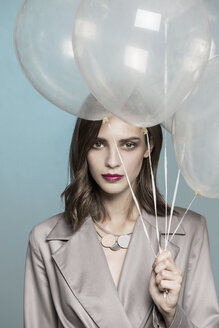Portrait of female fashion model holding balloons - FSIF03521