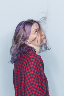 Young woman with dyed and tousled hair against blue background - FSIF03524