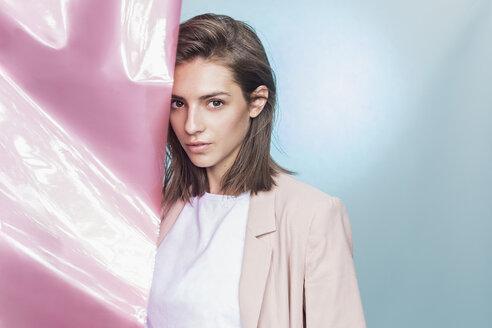 Portrait of a female fashion model posing with pink fabric - FSIF03530
