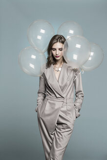 Portrait of female fashion model standing with balloons against blue background - FSIF03533