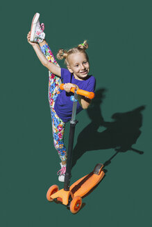 Playful girl with scooter doing standing splits on green background - FSIF03542