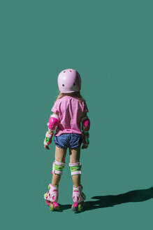 Girl roller skating on green background - FSIF03545