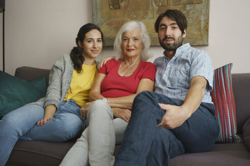 Portrait senior mother sitting with daughter and son on living room sofa - FSIF03557