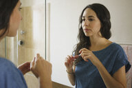 Woman applying lip gloss in bathroom mirror - FSIF03593
