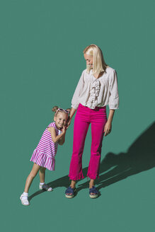 Portrait mother and daughter holding hands against green background - FSIF03632