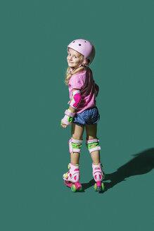 Portrait smiling girl roller skating against green background - FSIF03638