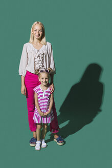 Portrait smiling mother and daughter against green background - FSIF03644