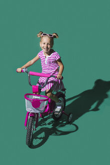 Portrait smiling girl bike riding against green background - FSIF03650
