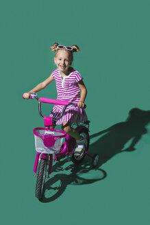 Portrait smiling girl bike riding against green background - FSIF03650