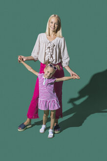 Portrait mother and daughter holding hands against green background - FSIF03653