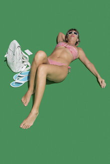Woman in bikini sunbathing on green background - FSIF03659
