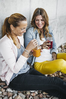 Two female friends drinking smoothies outdoors having fun - HMEF00166