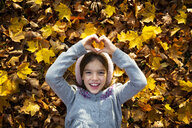 Portrait of happy little girl lying on autumn leaves shaping heart with her hands - LVF07605