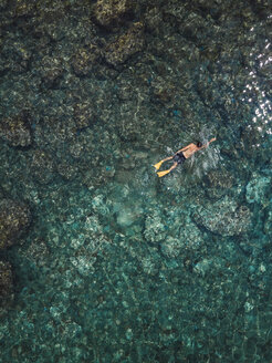 Indonesia, Bali, Man swimming in ocean at Amed beach - KNTF02587
