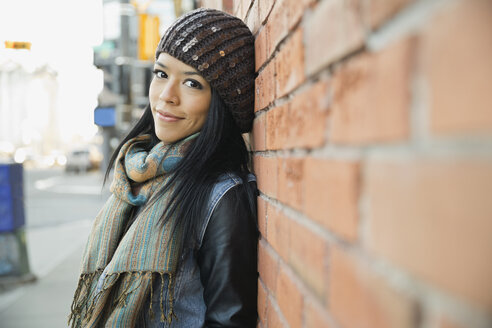 Portrait of woman leaning against brick wall - HEROF00615