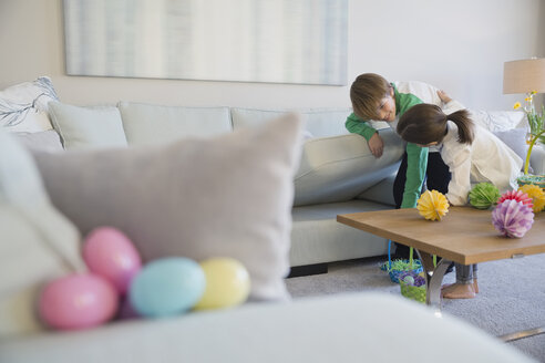 Siblings searching for Easter eggs in living room - HEROF00699