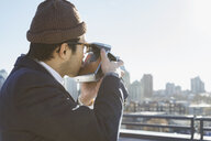 Side view of man photographing cityscape from patio - HEROF00717