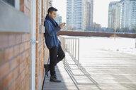Man text messaging using smart phone outdoors - HEROF00858