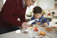 Grandfather and grandson decorating Christmas cookies together - HEROF00879