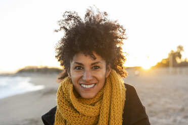 Portrait of a happy woman in the beach, wearing a yellow scarf - AFVF02108