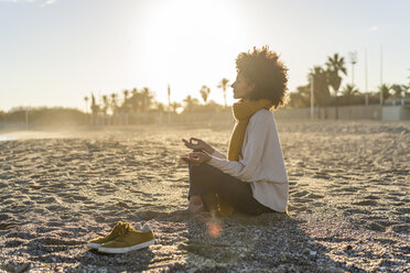 Woman sitting on the beach at sunset, meditating - AFVF02114