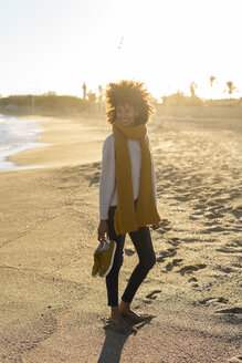 Barefoot woman on the beach, carrying her shoes - AFVF02123