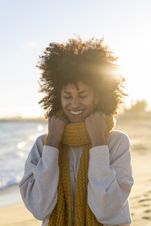 Portrait of a happy woman in the beach, wearing a yellow scarf - AFVF02126