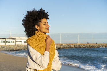 Portrait of a happy woman in the beach, wearing a yellow scarf - AFVF02129