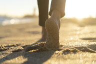 Bare feet of a woman, walking on the beach - AFVF02141
