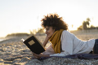 Woman lying in the sand, relaxing on the  beach, reading a book - AFVF02150