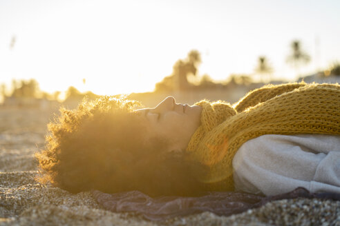 Woman lying in the sand, relaxing on the  beach - AFVF02156