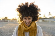 Portrait of a happy woman in the beach, wearing a yellow scarf - AFVF02165