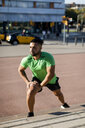 Sportive man during workout, stretching on steps - MAUF01962
