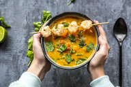 Girl's hands holding bowl of sweet potato soup with  shrimps, coconut flakes and fresh coriander - SARF04021