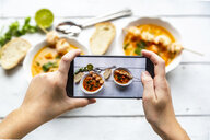 Girl taking photo of bowls with sweet potato soup with smartphone, close-up - SARF04024