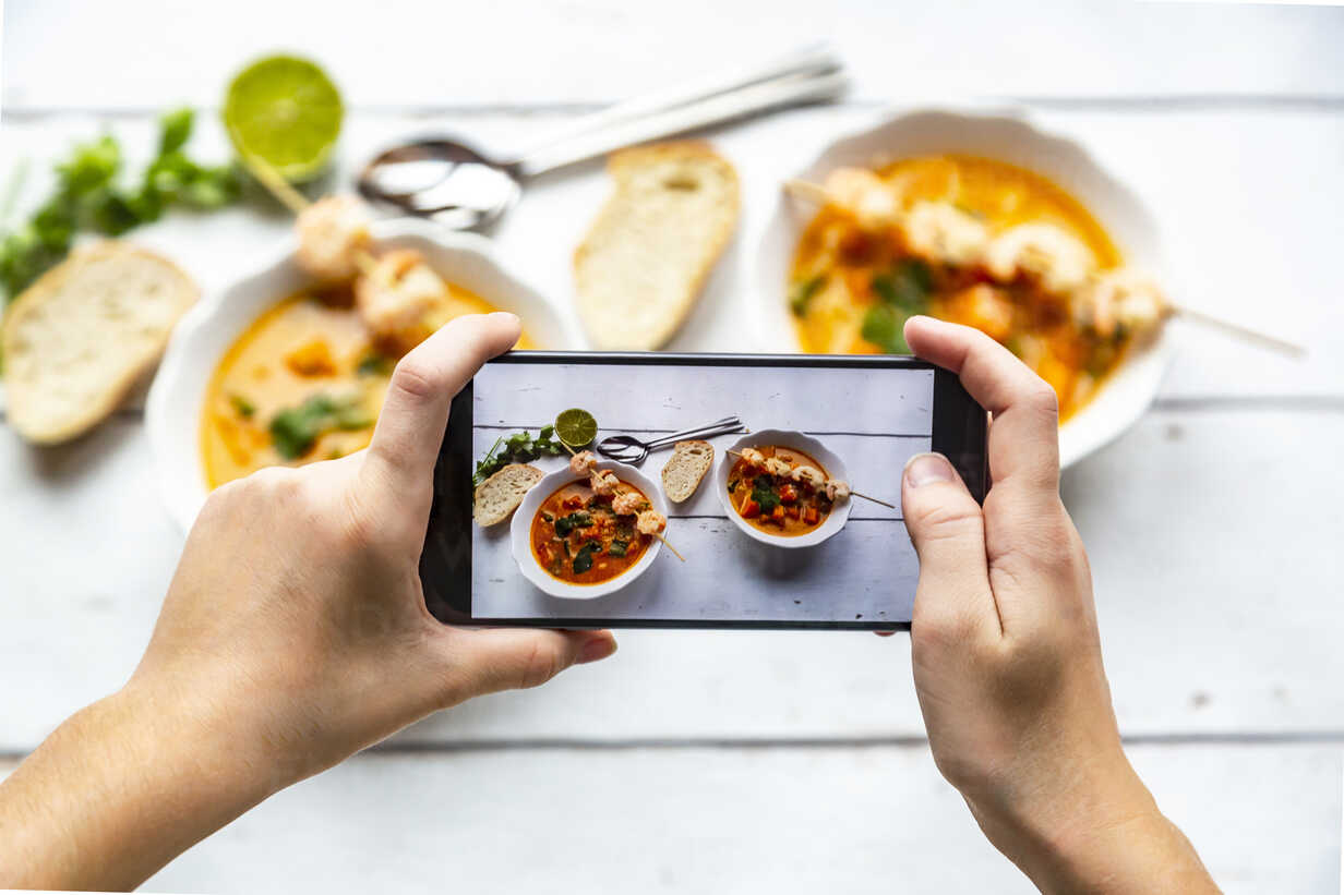 Girl taking photo of bowls with sweet potato soup with smartphone, close-up - SARF04024 - Sandra Roesch/Westend61