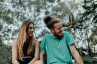 A young couple laughing in the forest - INGF10446