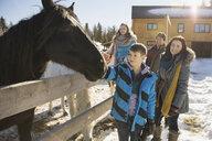 Family visiting horses on winter ranch - HEROF01028
