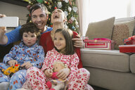 Family taking self portrait at home during Christmas - HEROF01052