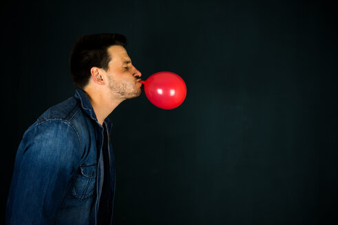 Side view of a young man blowing up a red balloon - INGF10589