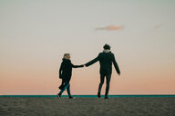 Full length shot of a young couple walking on the beach at sunset - INGF10661